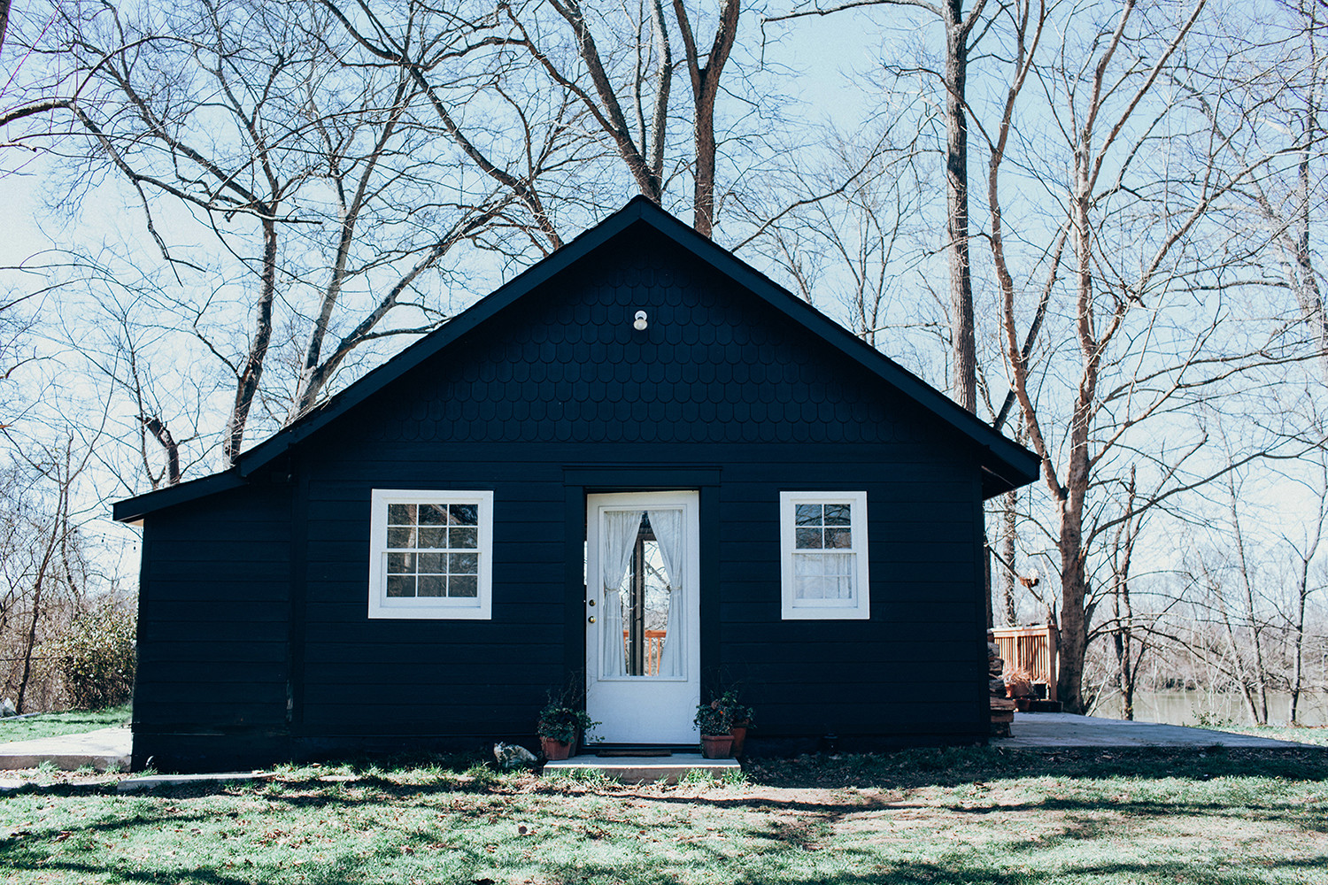 The exterior of the cottage is painted a deep, inky black color. Its crisp-white door and windows provide accent against the moody-toned paint job. All photos byEmily Dorio.