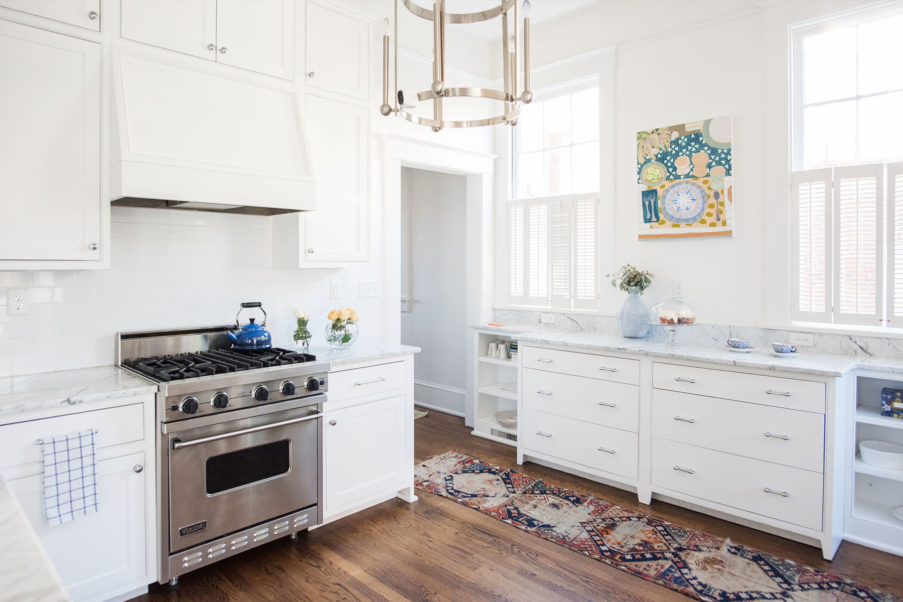 The open family kitchen isn't short on southern charm. Clutter Rug | Circa Chandelier | Homegoods Vases | Le Creuset Teapot | Waterworks Appliances | Lulie Wallace Artwork.