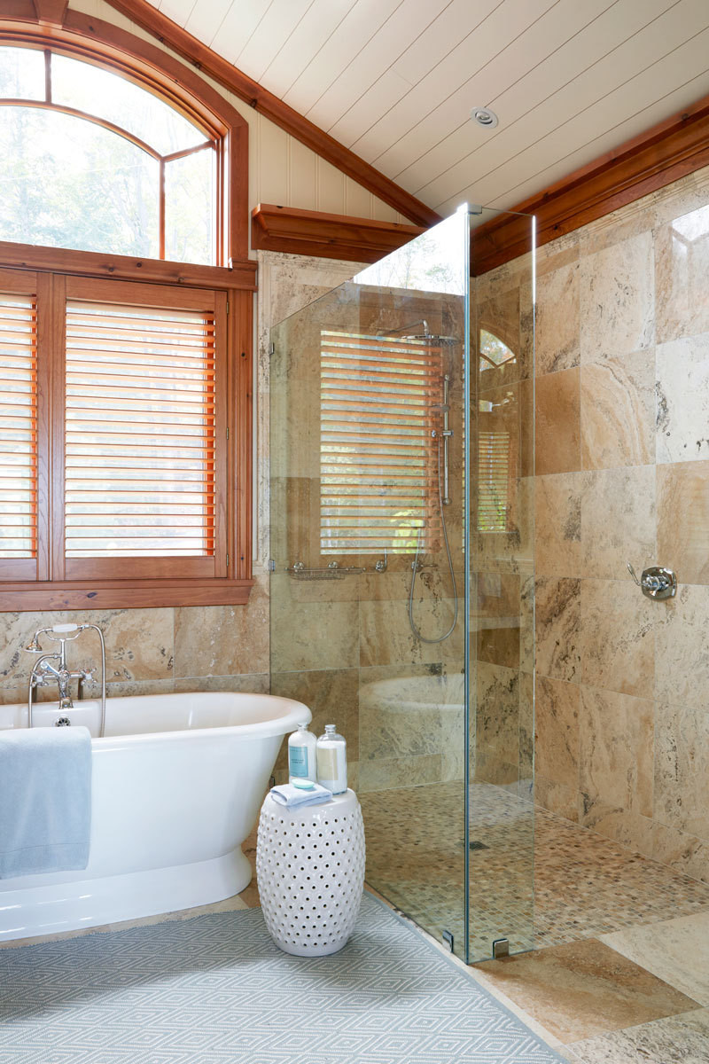 Shower walls of clear glass preserves the bathroom's airy mood.