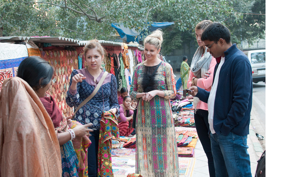 Birch Lane founder and design director Meredith Mahoney (center left) and head merchant Kerrie Morrison negotiate with a local shopkeeper near a fabric market.