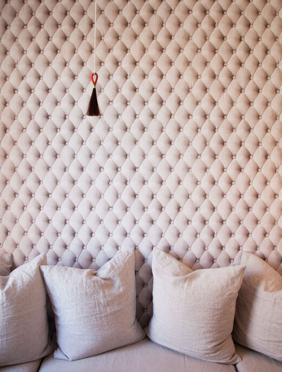 What appears to be a lushly tufted wall covering is in fact a clever use of wallpaper.