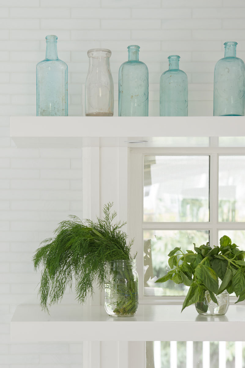 Open shelving in front of the kitchen windows makes for casual yet meaningful displays.