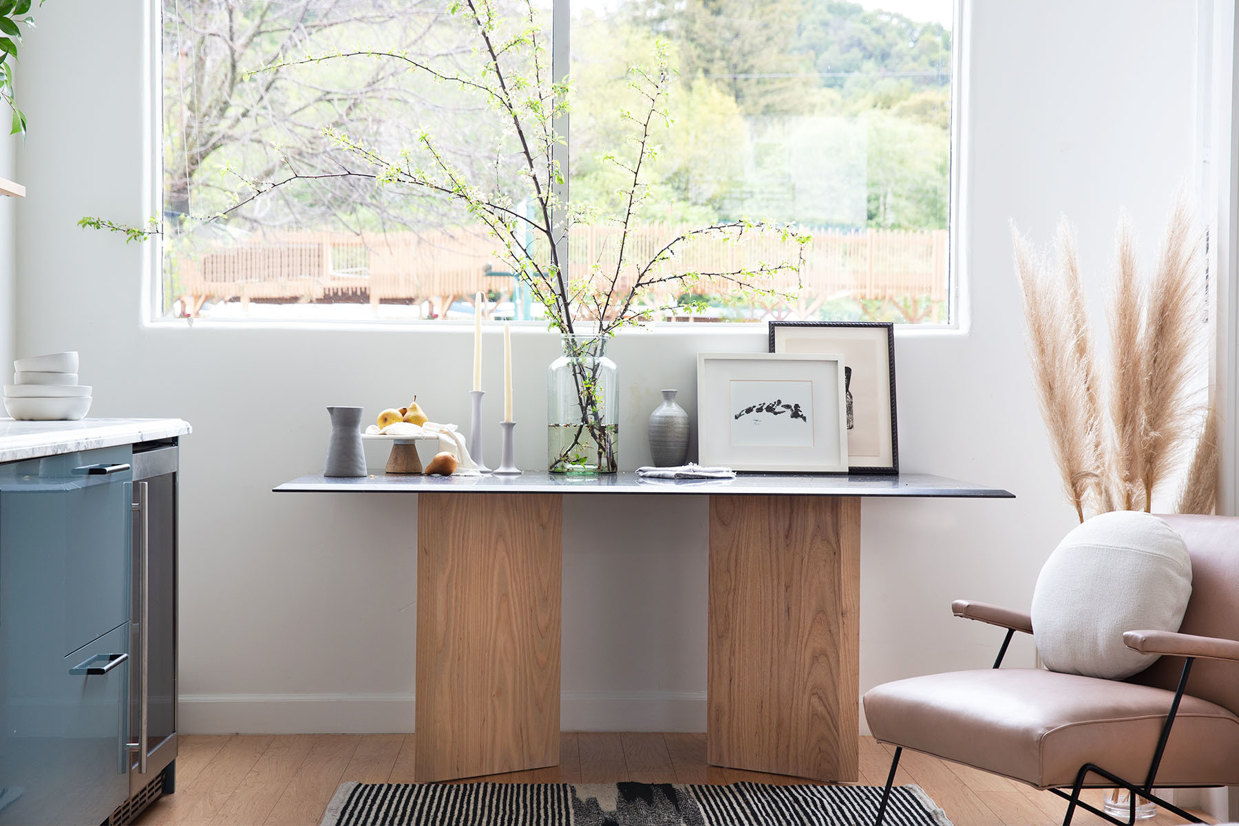 A custom table designed by Lauren Nelson and built by Kilomade Studios holds pride of place in the designer's San Anselmo studio. Fox Marble Counter | Target Ceramics | Elsie Green Vase | Target Cake Stand | Vintage Candlesticks | Vintage Frames.