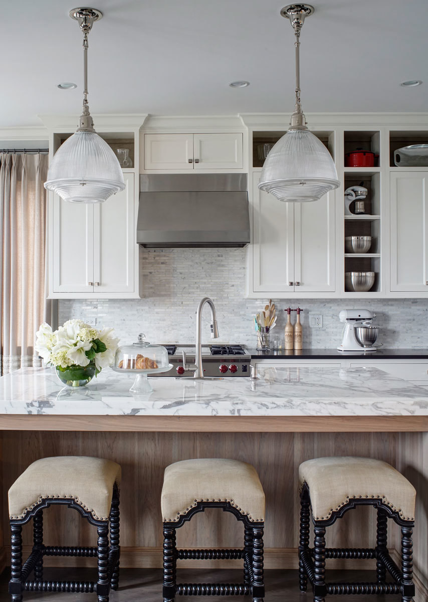 The open kitchen cleverly combines traditional cabinetry with of-the-moment factory lights and sleek marble countertops.