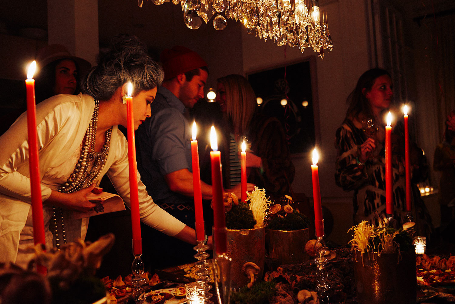 Costumed partygoers nibble on hors d'oeuvres arranged on a table lit by Creative Candles' towering tapers.